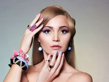Beauty portrait of girl with colorful Make-up. Beautiful Blonde Young Woman in color jewelry accessories royalty free stock photos