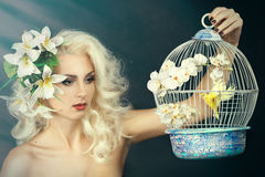 Beauty portrait of a girl with a lily in her hair. Blonde holding a cage with a bird. On a gray background Stock Image