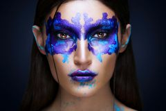 Beauty portrait of the girl with Rorschach test on her face. Mus. Woman in Creative makeup with Rorschach test on her face on dark background stock image