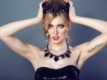 Beauty portrait of gorgeous blond model with updo hair wearing sequin strapless top and set of luxurious necklace and earrings. Holding black jewel crown on her Royalty Free Stock Images