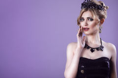 Beauty portrait of gorgeous young blond model in strapless sequin top with updo hair and black jewel crown on her head. Whispering something with her hand at Stock Image
