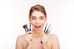 Beauty portrait of happy excited young woman with makeup brushes Royalty Free Stock Photography