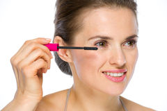 Beauty portrait of happy woman applying mascara Royalty Free Stock Image