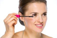 Beauty portrait of happy woman applying mascara royalty free stock image