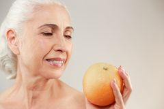 Beauty portrait of a lovely half naked elderly woman. Holding an orange isolated over white background Stock Photo