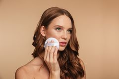 Beauty portrait of mystery ginger woman with long hair. Looking away while removing make up on her cheek over cream background Stock Images