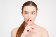 Beauty portrait of sensual attractive woman showing silence gesture. Beauty portrait of sensual attractive young woman  showing silence gesture over white Royalty Free Stock Photos