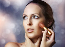Beauty portrait of woman applying cosmetics. Fashion beauty portrait of glamour young woman with perfect healthy skin applying cosmetics. Brunette female model royalty free stock images