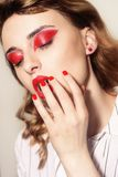 Beauty portrait of sexy women with glamour make up. Red lips and red eyeshadows, neils. Beauty fashion model face. Manicured hand stock photography
