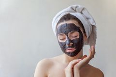 Woman applying mask on face stock image