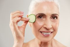 Beauty portrait of a smiling half naked elderly woman. Holding slice of fresh cucumber at her face and looking at camera isolated over white background Stock Photos