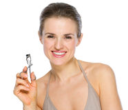 Beauty portrait of smiling holding eyelash curler Stock Image