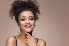 Beauty portrait of smiling sensual afro girl. Beauty portrait of young attractive african american woman with amazing toothy smile and glamour makeup Royalty Free Stock Photography