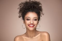 Beauty portrait of smiling sensual afro girl. Beauty portrait of young attractive african american woman with amazing toothy smile and glamour makeup Royalty Free Stock Image