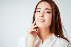 Beauty portrait of smiling sensual asian young woman with clean fresh skin in white shirt isolated. The Beauty portrait of smiling sensual asian young woman with stock image