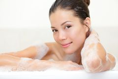 Beauty portrait of woman in bath. Tub with bath foam smiling happy looking serene at camera. Beautiful young mixed race Caucasian / Asian woman Stock Photography