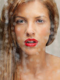 Beauty portrait of woman behind wet window Royalty Free Stock Photography