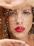 Beauty portrait of woman behind wet window Royalty Free Stock Images