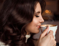 Beauty portrait of a woman drinking coffee. The concept of delicious coffee, cappuccino, mochaccino, mocha. Amazing Stock Photography