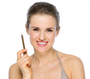 Beauty portrait of woman holding brown eye liner Royalty Free Stock Image