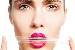 Makeup testing. Beauty portrait of woman holding laboratory test tube in her lips isolated on white Royalty Free Stock Images