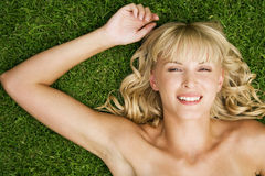 Beauty portrait of a woman laying in the grass in a tropical setting. Stock Photo