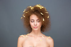 Beauty portrait of woman with petals on voluminous curly hairstyle Royalty Free Stock Photo