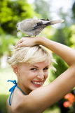 Beauty portrait of a woman in a tropical setting with a dove on her head. Stock Photos