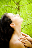 Beauty portrait of a woman in a tropical setting touching her neck. Royalty Free Stock Photos