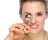 Beauty portrait of woman using eyelash curler Stock Photography