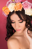 Beauty portrait of a woman with a wreath of flowers on her head a red background Stock Image