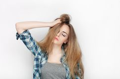 Beauty portrait of young adorable fresh looking blonde woman in blue plaid shirt. Emotion and facial expression concept. Stock Image