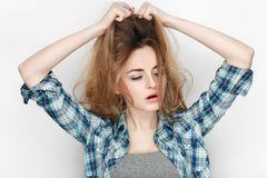 Beauty portrait of young adorable fresh looking blonde woman in blue plaid shirt. Emotion and facial expression concept. Royalty Free Stock Photography