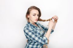 Beauty portrait of young adorable fresh looking blonde woman in blue plaid shirt. Emotion and facial expression concept. Royalty Free Stock Photo