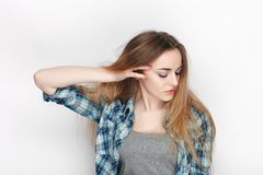 Beauty portrait of young adorable fresh looking blonde woman in blue plaid shirt. Emotion and facial expression concept. Stock Photo