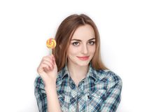 Beauty portrait of young adorable fresh looking blonde woman in blue plaid shirt posing with candy lollipop. Emotion and facial ex Stock Image