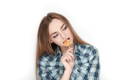Beauty portrait of young adorable fresh looking blonde woman in blue plaid shirt posing with candy lollipop. Emotion and facial ex Royalty Free Stock Images