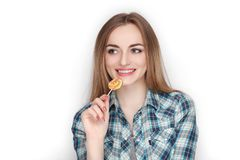 Beauty portrait of young adorable fresh looking blonde woman in blue plaid shirt posing with candy lollipop. Emotion and facial ex Stock Photo