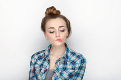 Beauty portrait of young adorable fresh looking blonde woman with high bun hair chaos in blue plaid shirt. Emotion and facial expr Stock Images