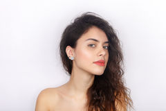 Beauty portrait of young adorable fresh looking brunette woman with healthy curly hair inquiring looks into camera. Emotion and fa Royalty Free Stock Image