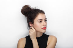Beauty portrait of young adorable fresh looking brunette woman with high bun hairdo touching her ear. Emotion and facial expressio Stock Image