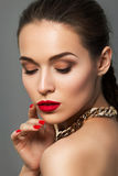 Beauty portrait of young aristocratic woman with red lips. And nails. Classic evening make up. Brown smokey eyes Royalty Free Stock Photography