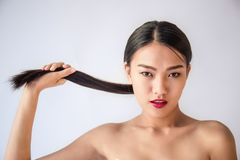 Beauty portrait of young asian woman with her hand pulling her long black hair royalty free stock photography