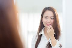 Beauty of portrait of young asian woman at the mirror holding and looking a makeup lipstick. royalty free stock images