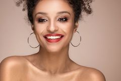 Beauty portrait of smiling sensual afro girl. Beauty portrait of young attractive african american woman with amazing toothy smile and glamour makeup Stock Photography