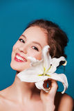 Beauty portrait of young, attractive woman with the lily flower on blue Stock Photos