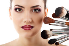 Beauty portrait of young beautiful woman with makeup brushes Royalty Free Stock Images