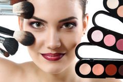 Beauty portrait of young beautiful woman with makeup brushes and Stock Photography