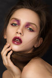 Beauty portrait of young brunette woman. With modern salon makeup. Golden and purple eyeshadows and fuzzy lip contour Stock Photos