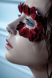 Beauty portrait of young fashion model with wet hairs and red fl. Ower petals around her eyes. studio shot on blue background stock photo